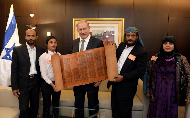 """Israeli Prime Minister Benjamin Netanyahu holds an 800 hundred years old torah scroll as he poses for a picture with Yemenite jews who were brought to Israel earlier this morning as part of a secret rescue operation, at the Knesset, the Israeli parliament in Jerusalem, March 21, 2016. Photo by Haim Zach/GPO *** Local Caption *** ??? ?????? ?????? ?????? ???? ?? ???? ???? ?????? ??? ????? ???? ???? ????? ??? ?? ??? ???? ??? 800 ???  ????? ???? ?? / ??""""?"""