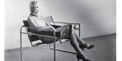 Erich Consemüller, Woman in B3 club chair by Marcel Breuer wearing a mask by Oskar Schlemmer, ca. 1926 black-and-white photograph Photo © Stefan Consemüller / Bauhaus-Archive Berlin
